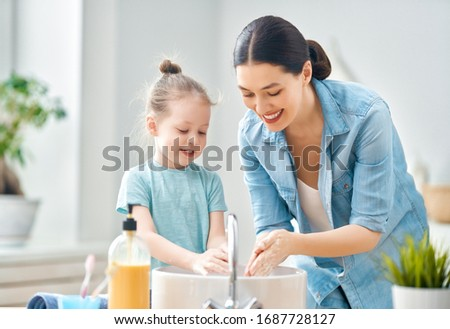 A cute little girl and her mother are washing their hands. Protection against infections and viruses. BAKU, AZERBAIJAN - MARCH 20, 2020 #1687728127