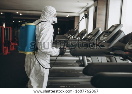 Cleaning and Disinfection in crowded places amid the coronavirus epidemic Gym cleaning and disinfection Infection prevention and control of epidemic. Protective suit and mask and spray bag #1687762867
