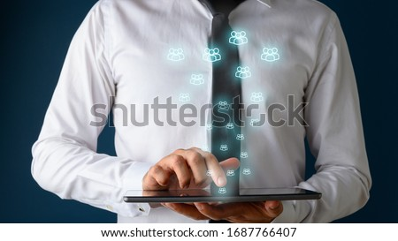 Front view of a businessman using digital tablet with many glowing people icons coming out of it. Conceptual of customer service and social media interactions.