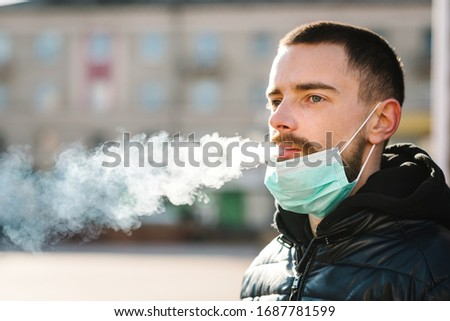 Coronavirus. Smoking. Closeup man with mask during COVID-19 pandemic smoking a cigarette at the street. Smoking causes lung cancer and other diseases. The dangers and harm of smoking. #1687781599