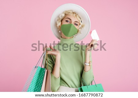 Spring online shopping during quarantine conception: fashionable woman wearing protective mask posing with colorful paper bags and plastic bank card. Pink background. Copy, empty space for text #1687790872