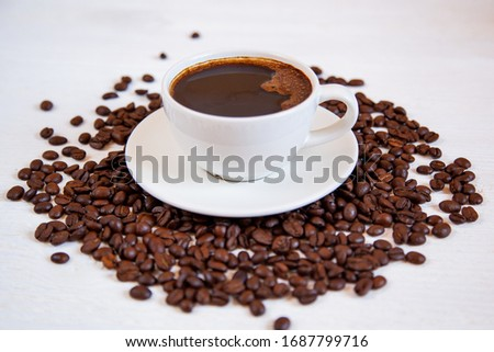White cup of coffee stands on coffee beans. #1687799716