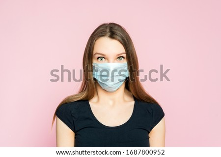 Coronavirus, masked woman.Studio portrait of a young woman wearing a face mask, looking at camera, on pink background. #1687800952