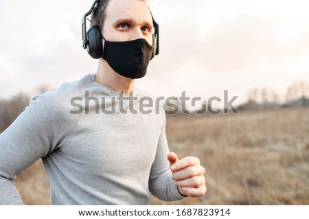 Sport during quarantine, self-isolation in the countryside. A young athletic guy is jogging on a dirt road in the meadow. He is wearing a black medical mask and headphones #1687823914