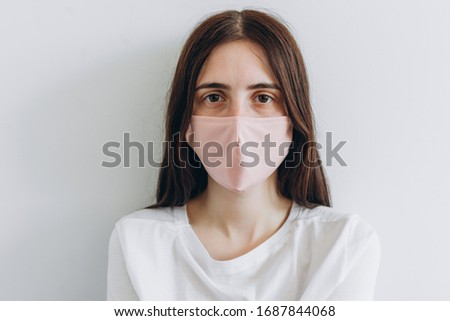 girl in a pink medical mask looks forward. girl dressed in a white t-shirt on a white background. #1687844068