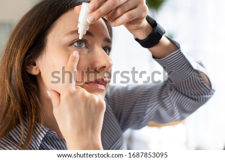 Young business woman uses eye drops for eye treatment. Redness, Dry Eyes, Allergy and Eye Itching #1687853095
