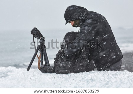 Photographer changing lens in challenging conditions in a snow storm using a beached iceberg as a convenient table. DSLR camera with open lens mount detached