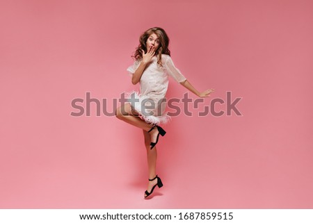Surprised woman in white dress jumps on pink background. Happy shocked girl covers mouth and moves on isolated. #1687859515