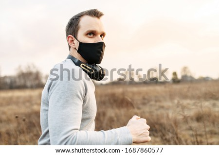 Sport during quarantine, self-isolation in the countryside. A young athletic guy is jogging on a dirt road in the meadow. He is wearing a black medical mask and headphones. Motion photo