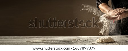 Photo of flour and men hands with flour splash. Cooking bread. Kneading the Dough. Isolated on dark background. Empty space for text. #1687899079