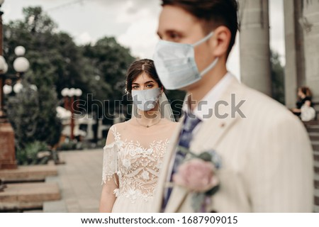 Young loving brides walking in the city in medical masks during quarantine on their wedding day. Coronavirus, disease, protection, sick, illness Royalty-Free Stock Photo #1687909015