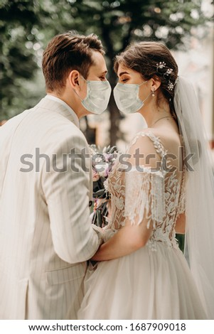 Young loving brides walking in the city in medical masks during quarantine on their wedding day. Coronavirus, disease, protection, sick, illness #1687909018