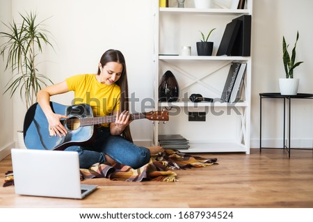 Hobbies and leisure activities during quarantine. Online training, online classes. A young woman watches a video lesson on playing the guitar, she sits on a cozy plaid with a guitar #1687934524