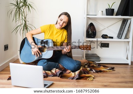 Online training, online classes. A young woman watches video tutorial on guitar playing, she sits on a cozy plaid with a guitar Royalty-Free Stock Photo #1687952086