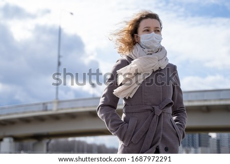young European woman in protective disposable medical mask walking  in deserted city street outdoor. concept of coronavirus influenza covid-19 quarantine and people panic. apocalypse sky Royalty-Free Stock Photo #1687972291