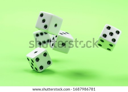A conceptual photo of dice being rolled on a green table. #1687986781
