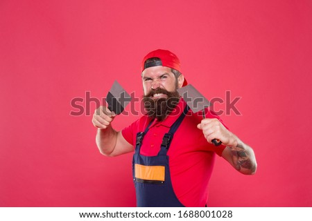 Professional plasterer. Skillful plasterer. Successful renovation. Repair success. Bearded man worker with plastering tools. Plasterer hipster builder in cap red background. Interior designer. #1688001028