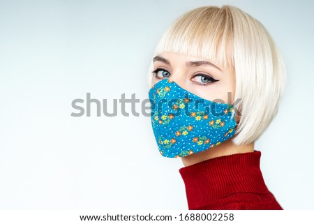 Woman wearing stylish handmade protective face mask. Fashion during quarantine of coronavirus outbreak. Copy, empty space for text #1688002258