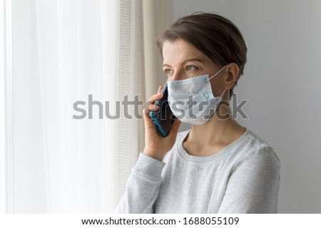 A young woman in a medical mask in quarantine is talking on the phone. outbreak concept #1688055109