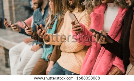 Group of young multi-ethnic people using smartphone sitting in a bench. Multiracial people holding smart mobile phones and watching their screen outdoors. #1688058088