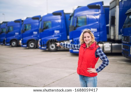 Female trucker standing in front of parked trucks and pointing her finger to the transportation vehicles. Transportation service. #1688059417
