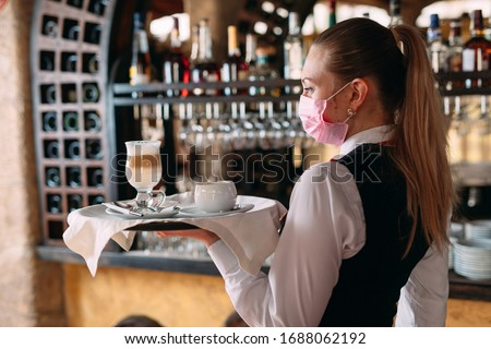 A female Waiter of European appearance in a medical mask serves Latte coffee Royalty-Free Stock Photo #1688062192