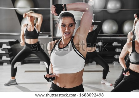 Women in black and white sportswear on a real group body Combat workout in the gym train to fight, kickboxing with a trainer Royalty-Free Stock Photo #1688092498