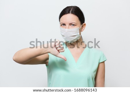 Nurse girl with thumb down in medical face mask, epidemic, coronavirus, air pollution, coronavirus 2019-November, crown virus quarantine concept, Covid-19.Girl on a white background #1688096143