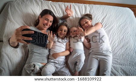 Authentic shot of happy mother with her kids are making a selfie or video call to father or relatives in a bed. Concept of technology, new generation,family, connection, parenthood, authenticity #1688109922