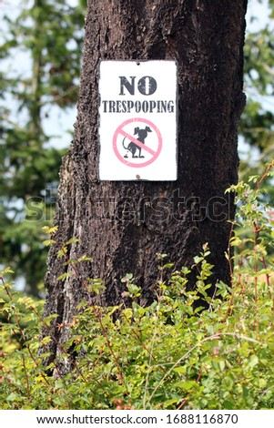 Whimsical dog no trespooping sign hung on a tree  #1688116870