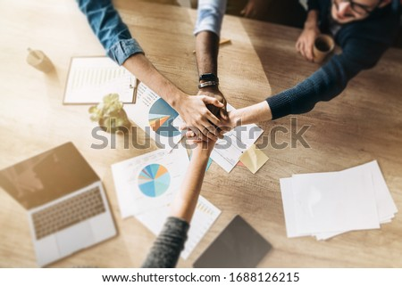 Business colleagues gathered at the same table during the work process, and rejoice in the success of their company. Top view Royalty-Free Stock Photo #1688126215