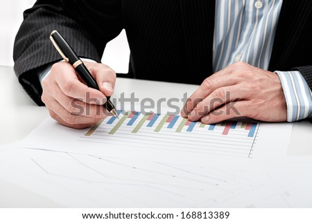 A man analyzing a bar chart writing notes with his pen #168813389