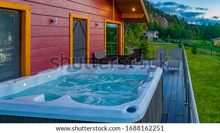 Wooden cottage with veranda for SPA treatments. Hot tub on the balcony of the country house. A place for relaxation. SPA treatments in the fresh air. Cottage on the background of the mountain. #1688162251