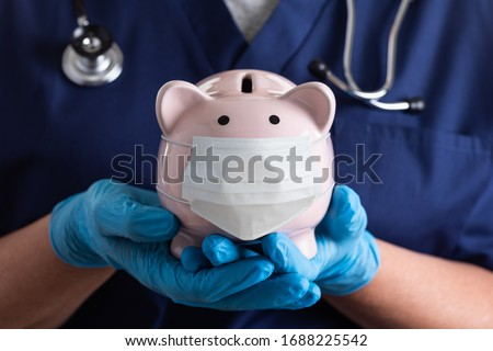 Doctor or Nurse Wearing Surgical Gloves Holding Piggy Bank Wearing Medical Face Mask. Royalty-Free Stock Photo #1688225542