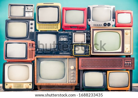 Retro TV receivers set from circa 60s, 70s and 80s of XX century, old wooden television stand with amplifier front mint blue wall background. Broadcasting, news concept. Vintage style filtered photo Royalty-Free Stock Photo #1688233435