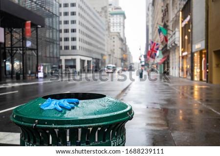 Used glove on empty street of New York City during Coronavirus quarantine lockdown Royalty-Free Stock Photo #1688239111