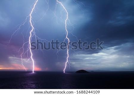 Double lightning strike over the ocean at sunset