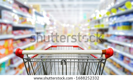 Supermarket aisle with empty red shopping cart. Royalty-Free Stock Photo #1688252332