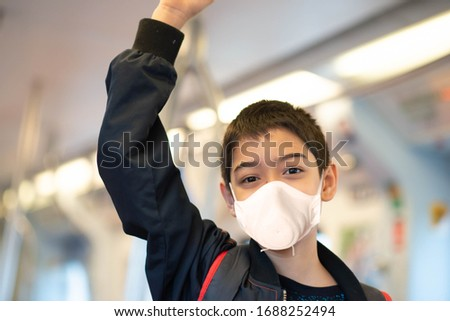 Little boy wear mask protect from virus buying electric ticket and walking in the public sky train station   #1688252494