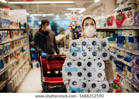 Woman shopper with mask and gloves panic buying and hoarding toilette paper in supply store.Preparing for pathogen virus pandemic quarantine.Prepper buying bulk cleaning supplies due to Covid-19. #1688252590
