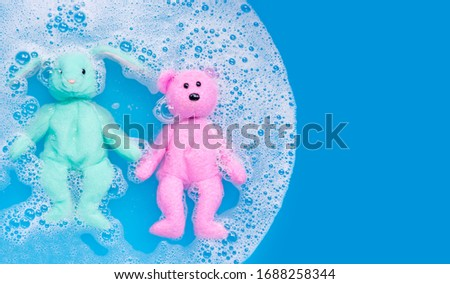 Soak rabbit doll with  toy teddy bear in laundry detergent water dissolution before washing.  Laundry concept, Top view #1688258344