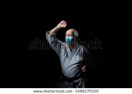 An old male athlete in a medical mask trains a block with his hand on a black background #1688270350