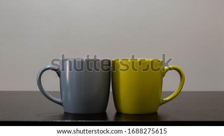 Green and blue cup mug placed on the wooden table #1688275615