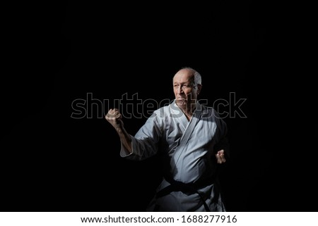 An old male athlete stands in a karate stance on a black background Royalty-Free Stock Photo #1688277916