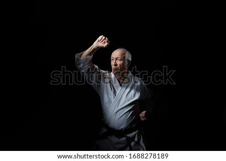 An old male athlete is training a block with his hand at an average level on a black background #1688278189