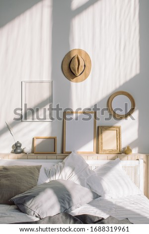 Cozy bedroom with various photo frames mockups hanging on white wall. Scandinavian interior.