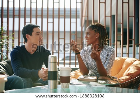 Positive emotional young businesswoman discussing news and ideas with colleague at meeting Royalty-Free Stock Photo #1688328106