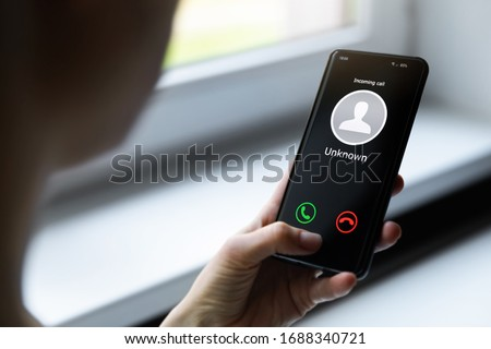 woman holding mobile phone with incoming call from unknown caller #1688340721