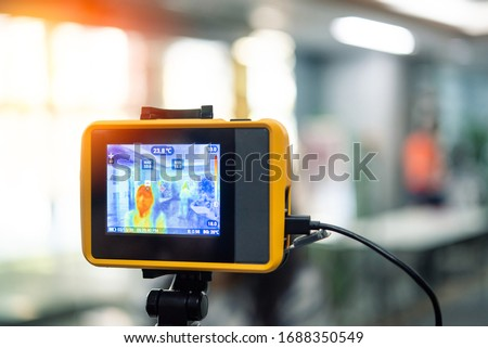 Asian people waiting for body temperature check before access to building for against epidemic flu covid19 or corona virus from wuhan in office by thermoscan or infrared thermal camera #1688350549