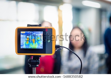 Asian people waiting for body temperature check before access to building for against epidemic flu covid19 or corona virus from wuhan in office by thermoscan or infrared thermal camera #1688350582